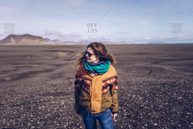Smiling human with standing between dark grounds in Iceland