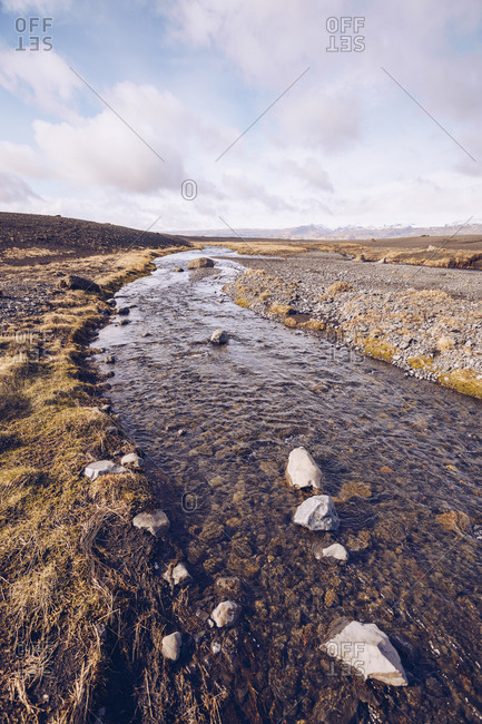 Mountain river streaming between brown grounds and view on lowland in Iceland