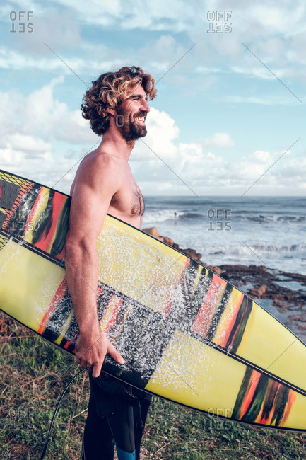 Young man with surf board near sea