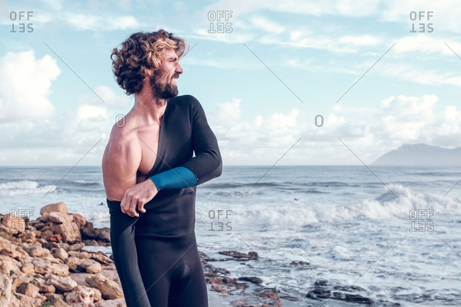 Young man putting on wetsuit near sea