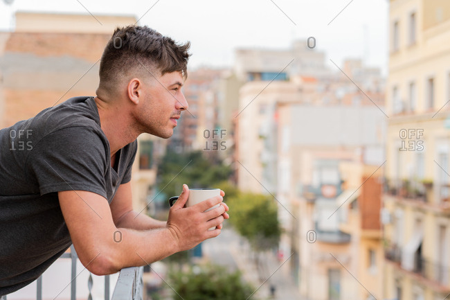 Side view of casual man holding mug of coffee and leaning on fence of balcony looking away