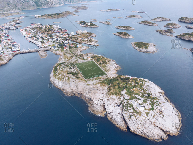 Drone view from height of Lofoten Islands with settlement and football field in blue ocean water, Norway