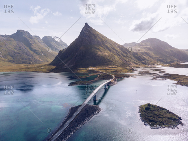 Picturesque drone view of mountains and roadway with bridge running among blue ocean water of Lofoten Islands