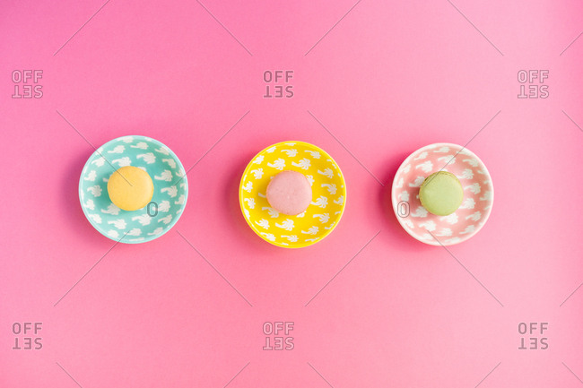 From above bright delicious macarons on plates on pink background
