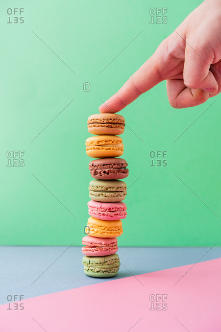 Male hand in silver bracelet with showing finger on pile of fresh tasty macarons on blue board on green background