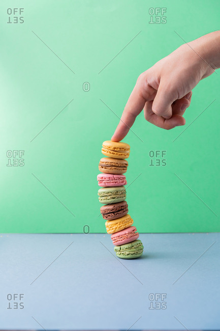 Male hand in silver bracelet with showing finger on falling pile of fresh tasty macarons on blue board on green background