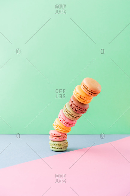 falling pile of fresh tasty macarons on blue board on green background