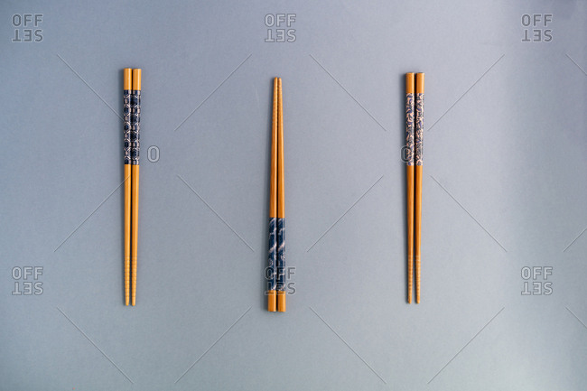 From above collection of wood chopsticks on blue background