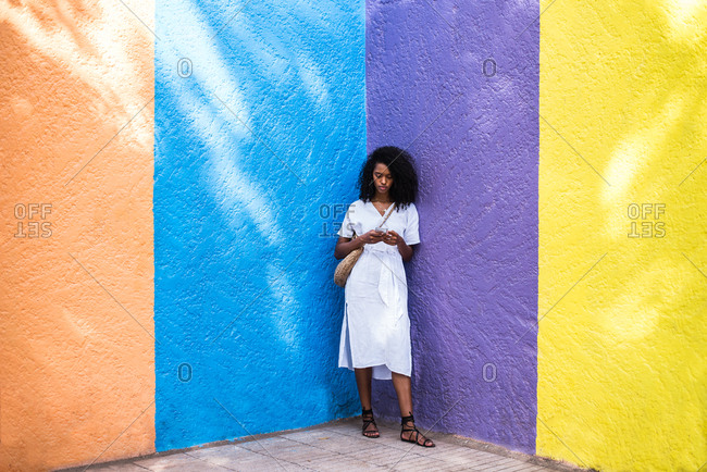 Black woman on the mobile phone in a colorful background
