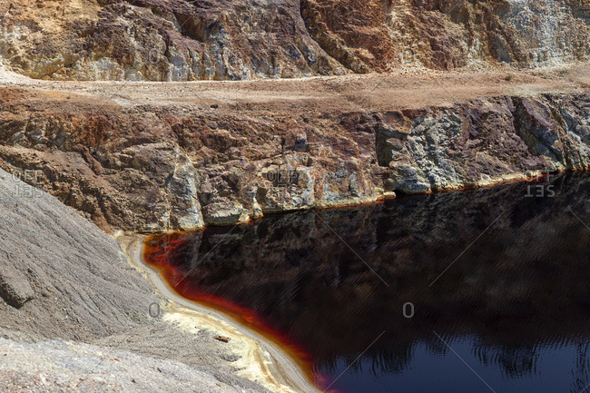 Calm surface of water near slope of quarry in Santo Domingos Mine, Portugal