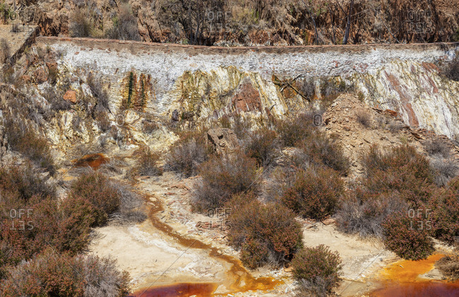 Small streams of dirty water flowing on slope of pit in Santo Domingos Mine in Portugal
