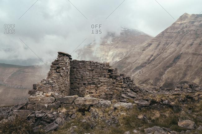 Brick building near peak of mountain between clouds