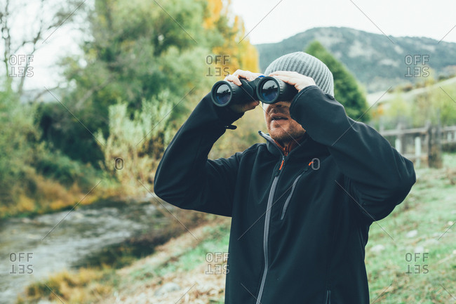 A young caucasian man with binoculars in the mountain in autumn colors