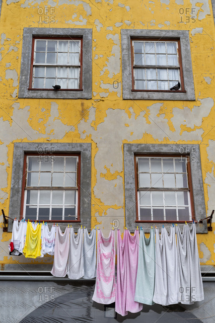 Old yellow facade of house with windows with gratings and clothes hanging on twist in Porto, Portugal