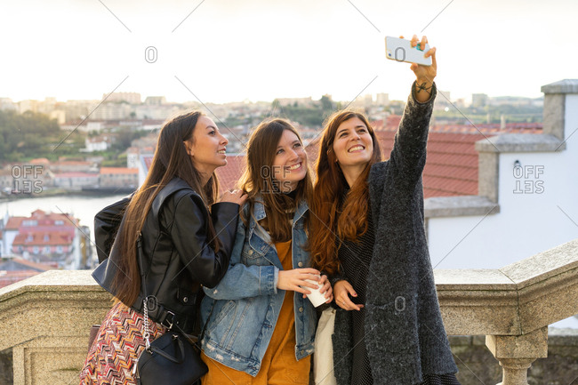Stylish attractive smiling ladies in casual wear taking selfie on smartphone on cityscape background in Porto, Portugal