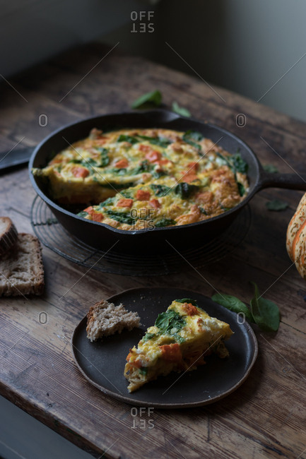 Plate and metal saucepan with delicious pumpkin and spinach frittata standing on timber tabletop