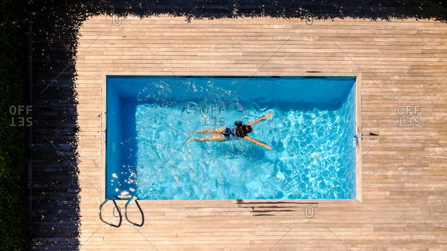 From above shot of unrecognizable female swimming in transparent water of pool while resting in resort