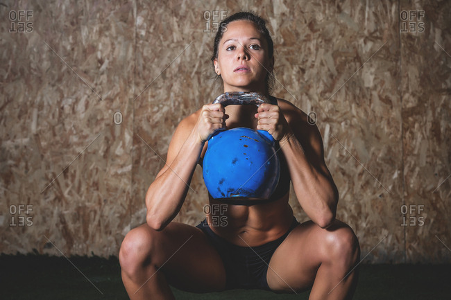 Woman with kettle bell in sports hall