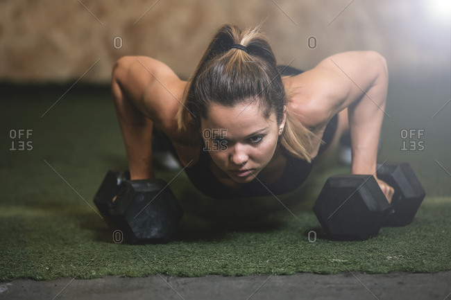 Woman in plank lifting dumbbell in sports hall