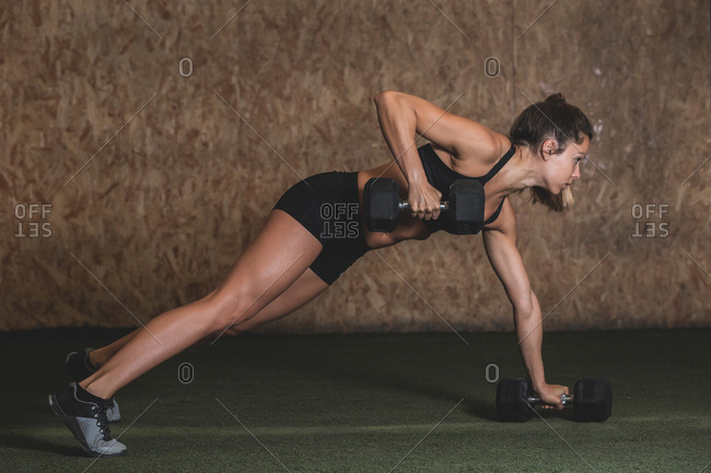 Side view young slim lady in sportswear doing dumbbells plank and lifting weight in gym