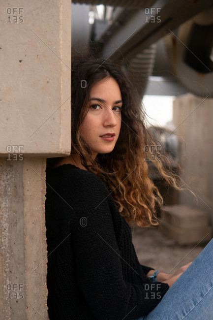 Side view of charming young female with curly hair looking at camera while sitting near wall of concrete building on city street