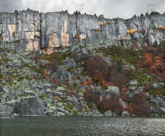 Picturesque view of amazing autumn trees growing on rough cliff near calm water in Soria, Spain