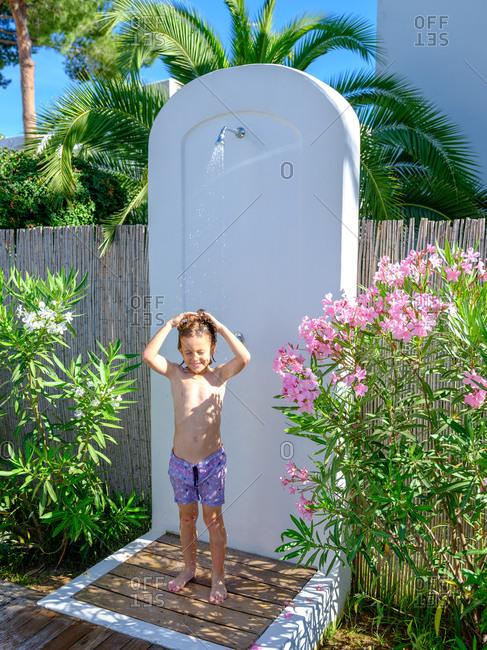 Cheerful boy taking shower in garden