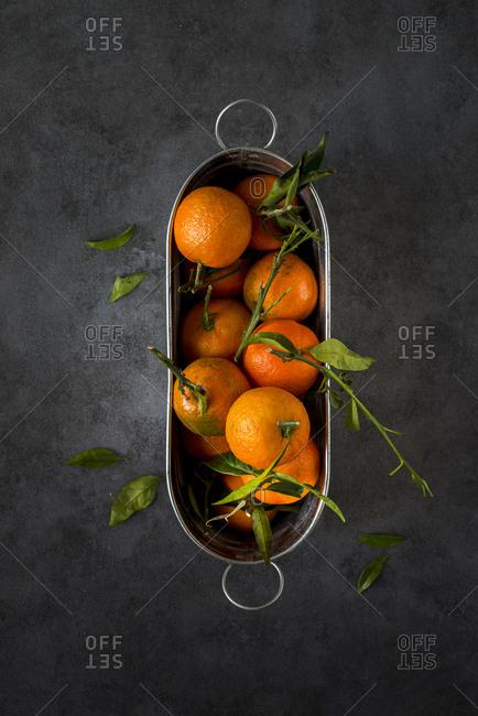 Tangerines in a metal bucket