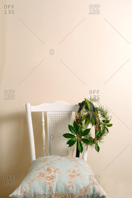Christmas green wreath hanging on white vintage chair, branches of pine and natural plants