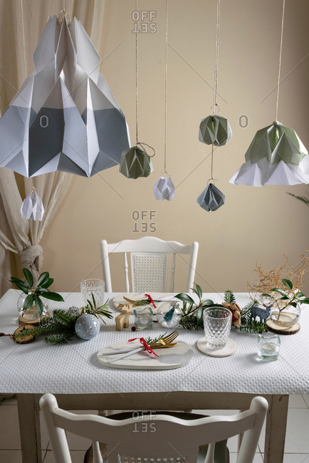Holiday celebration table setting, in white and gold colors, with hanging decorations decorating the table