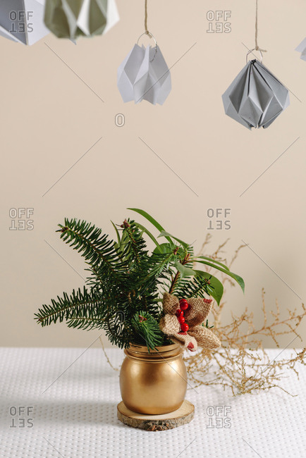 Christmas Tree in gold vase with Pine Branches Bouquet, home festive decor on the white table