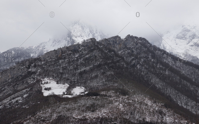Range of dark cold mountains with snow and haze