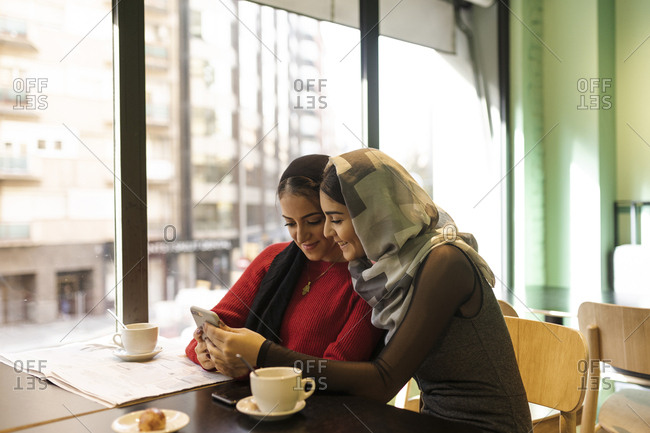 Two young women looking at cell phone together in a coffee shop