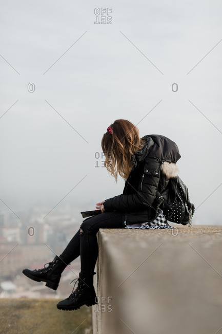 Girl sitting on ledge writing in journal