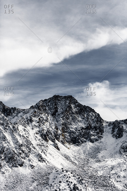 Dark skies and clouds over snowy mountains in Andorra