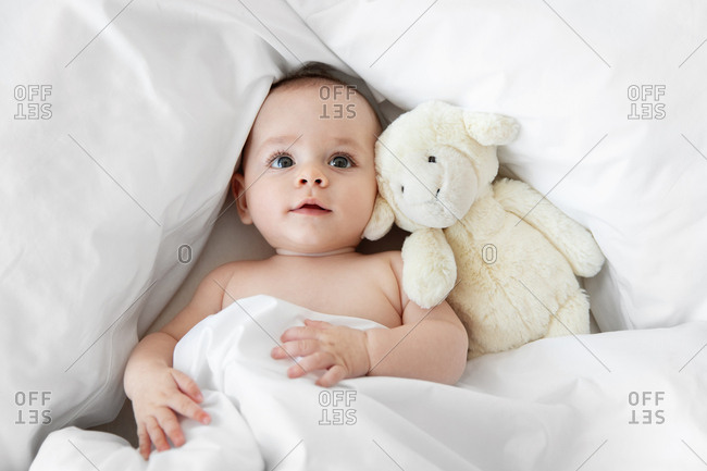 Overhead view of baby surrounded in white blankets and stuffed animal