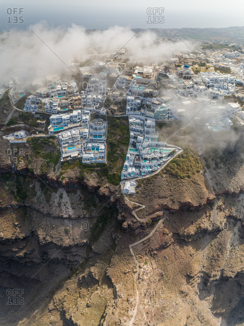 Aerial vertical view over the clouds of traditional white houses on Santorini island, Greece.