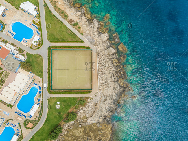 Aerial view of shore of resort with pools and tennis court on Rhodes island, Greece.
