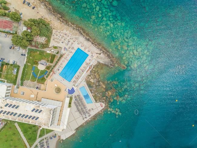 Aerial view of swimming pool next to sea on shore of Rhodes island, Greece.