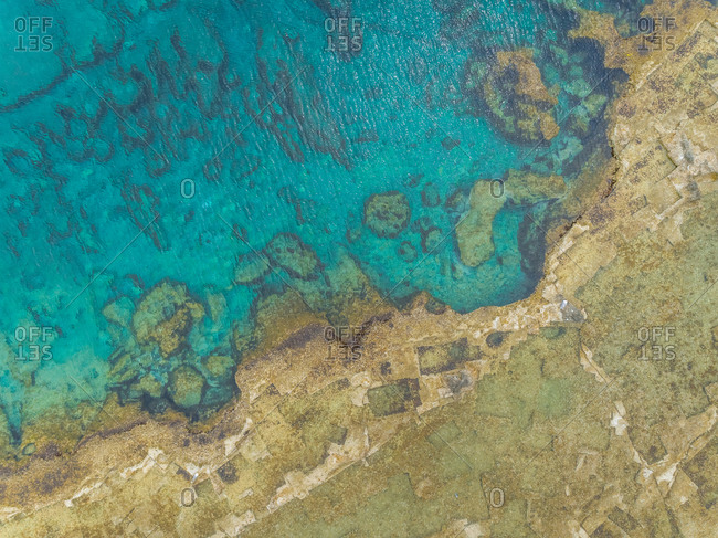 Aerial view of shore and rock formation under clear mediterrean sea, Rhodes island, Greece.