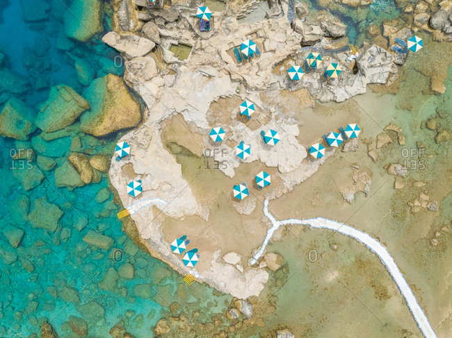 Aerial view of blue and white parasols on rocky coast, Rhodes island, Greece.
