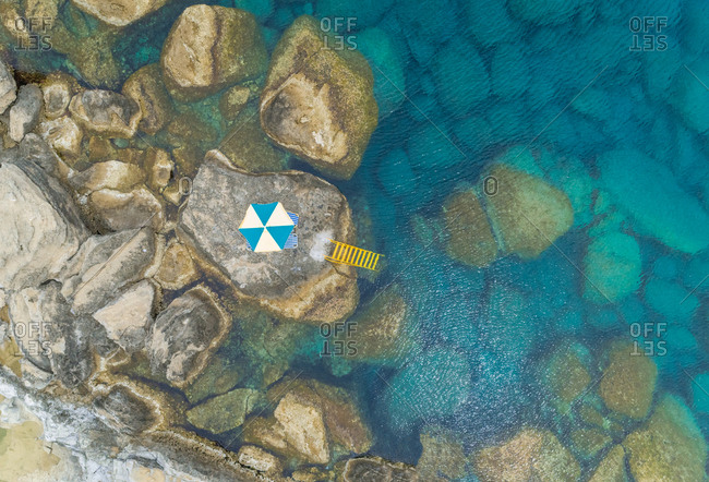 Aerial view of shore of Rhodes island with multicolored parasol and yellow ladder leading into sea, Greece.