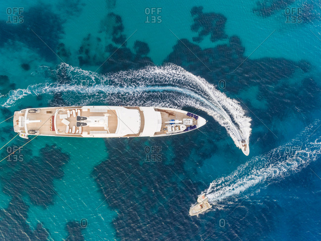 Aerial view of jet ski driving around luxurious yacht in the mediterranean sea, Mikonos island, Greece.
