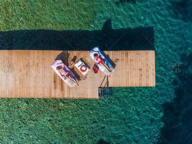 Aerial view of two attractive women sunbathing on wooden pontoon in Panagopoula, Greece.