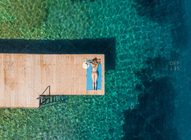 Aerial view of attractive woman sunbathing on wooden pontoon in Panagopoula, Greece.