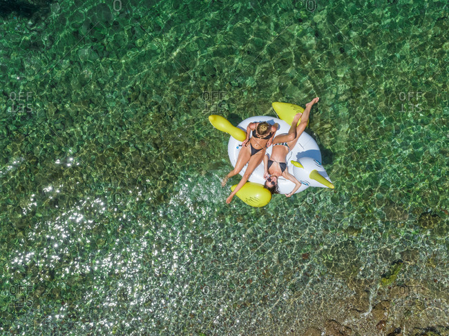 Aerial view of two women in bikinis floating on inflatable animal mattress in Panagopoula, Greece.