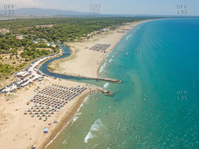 Aerial view of coastline with river entering sea with straw parasols on Achaia, Greece.