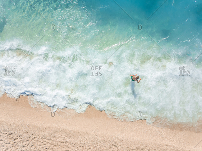 NIKITAS, GREECE - 13 JULY 2018: Aerial view of kid playing in waves on sandy beach in turquoise sea.