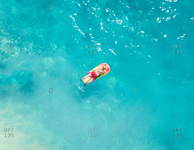 Aerial view of man floating on inflatable on beach, Greece.