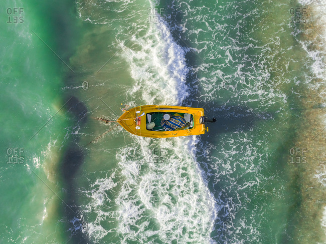 Aerial view of small yellow fishing boat moored on beach in the mediterranean sea, Monodendri, Greece.